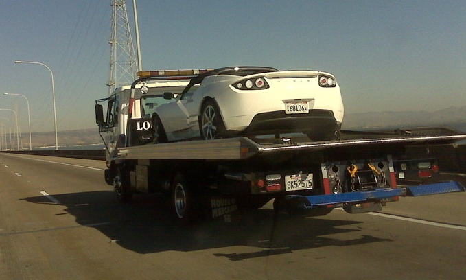 Inoperable Tesla Roadster being towed on a flatbed.